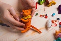 Le renard rouge de jouet a fait ses mains sur le fond en bois Photos stock