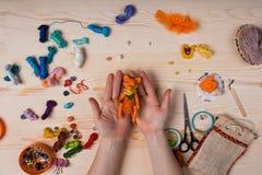 Le renard rouge de jouet a fait ses mains sur le fond en bois Images stock