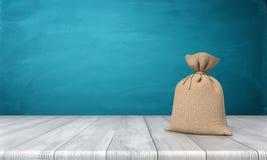le rendu 3d d'un blanc a attaché le sac hessois complètement de l'argent se tenant sur une surface en bois sur le fond bleu Photo libre de droits