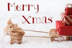 Le renne avec le traîneau sur la neige, textotent joyeux Noël Photos libres de droits