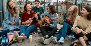 Le repaire d'amis chantent à mode de vie gratuit le hippie urbain Photo stock