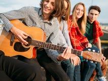 Le repaire d'amis chantent à mode de vie gratuit le hippie urbain Photos stock
