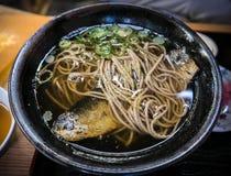 Le repas japonais, les nouilles chaudes de soba avec des harengs pêchent Images stock