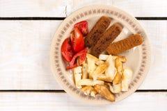 Le repas servi sur la table, chair de poissons frite colle avec les pommes de terre et la salade de tomate photo libre de droits