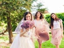 Le repos de jeune mariée et de demoiselles d'honneur Photo stock