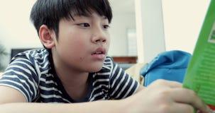 Le repos pré de l'adolescence d'Asiatique sur des bandes dessinées de plancher et de lecture réservent Soyez visage lisse banque de vidéos