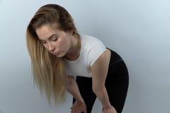 Le repos sportif de femme prend une respiration profonde après des exercis d'une séance d'entraînement images stock