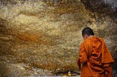 Le respect de moine priant et dorent la couverture avec la feuille d'or chez Lord Buddh photo libre de droits