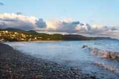 Le ressac faisant rage ondule sur la plage contre le ciel nuageux de la côte montagneuse Photo stock