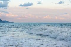 Le ressac faisant rage ondule sur la plage le soir après la tempête de la côte montagneuse Photo libre de droits