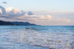 Le ressac faisant rage ondule sur la plage le soir de la côte montagneuse Photographie stock