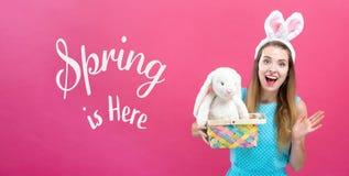 Le ressort est ici message avec la femme avec le panier de Pâques photos libres de droits