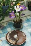 Le ressort fleurit les crocus et le gâteau pourpres sur une table par la fenêtre Photos stock