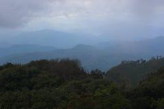 Le ressort foncé de vallée de montagne de brouillard et de nuage aménagent en parc Photos stock