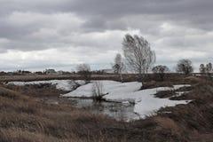 Le ressort froid sombre dans le paysage nuageux de la Sibérie fond la neige dans les domaines photographie stock