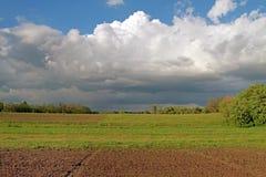 Le ressort a labouré le champ sur un fond d'herbe verte et de tre vert Image stock