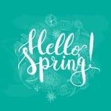 Le ressort tiré par la main d'expression de lettrage de typographie bonjour sur le fond bleu avec les fleurs de floraison tressen Photo libre de droits