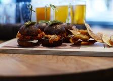 Le restaurant a plaqué le plat, les hamburgers de glisseur et les pommes chips Photographie stock libre de droits