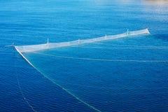 Le reti da pesca hanno allungato nel mare, il concetto dell'impresa di piscicoltura Fotografia Stock