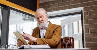 Le retraité apprend comment utiliser le comprimé Image libre de droits