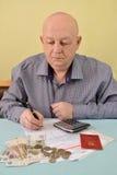 Le retraité compte des dépenses en espèces pour des paiements de service photographie stock libre de droits