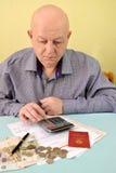 Le retraité compte sur les dépenses en espèces de calculatrice pour des paiements de service photo libre de droits