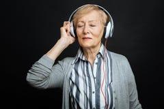 Le retraité paisible appréciant la musique dans le noir a coloré le studio Images stock