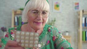 Le retraité recherche l'information sur l'Internet au sujet des pilules se reposant à la fin de table  clips vidéos