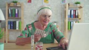 Le retraité recherche l'information sur l'Internet au sujet des pilules se reposant à la table banque de vidéos