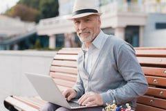 Le retraité s'assied sur le banc et travaille derrière l'ordinateur portable Il s'assied sur un banc dans l'allée Photo stock