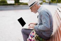 Le retraité s'assied sur le banc et travaille derrière l'ordinateur portable Il s'assied sur un banc dans l'allée Photos libres de droits