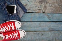 Le retro scarpe da tennis e smartphone rossi in jeans intascano su un wo blu Fotografia Stock