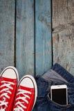 Le retro scarpe da tennis e smartphone rossi in jeans intascano su un wo blu Immagine Stock Libera da Diritti