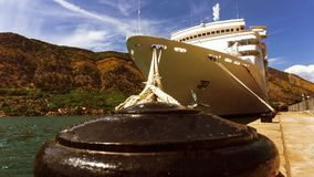 Le revêtement de croisière est amarré au pilier dans le port dans une baie entourée par des montagnes image stock