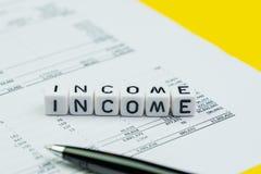 Le revenu, le revenu de société ou le concept de profits et pertes de rapport, cubent de petits blocs avec l'alphabet établissant image libre de droits