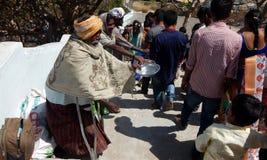 Le ricerche indù indiane dell'uomo senior aiutano o elemosine o elemosina sulle scale del tempio immagini stock libere da diritti