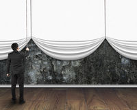 Le rideau blanc vide ouvert en traction d'homme d'affaires a couvert le béton sale Photo stock