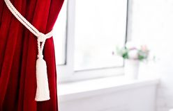 Le rideau en claret rassemblé par une dentelle décorative près d'une fenêtre image libre de droits