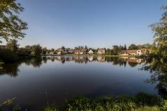 Le riflessioni di piccole case del villaggio in stagno innaffiano Fotografia Stock Libera da Diritti