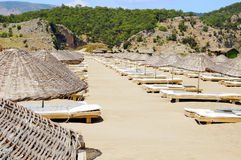 Le righe degli ombrelli della paglia sulla spiaggia vuota tirano Immagini Stock