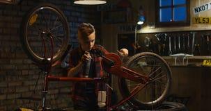 Le riparazioni teenager del ragazzo vanno in bicicletta fotografia stock libera da diritti