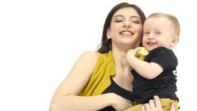 Le risate del bambino, in sue mani tiene una mela ed i suoi giri della madre Priorità bassa bianca Movimento lento video d archivio