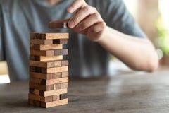 Le risque se produira Main d'ingénieur jouant un jeu en bois de blocs sur le ton en bois de vintage de table Projet architectural images libres de droits