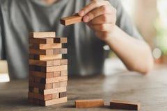 Le risque se produira Main d'ingénieur jouant un jeu en bois de blocs sur le ton en bois de vintage de table Projet architectural image stock