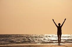Le riuscite braccia della donna si sono alzate al tramonto sulla spiaggia Fotografie Stock