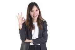 Le riuscite donne di affari in sorriso del vestito e mano giusta firmano su fondo bianco Fotografie Stock