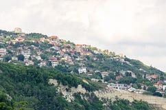 Le rivage de la Mer Noire, collines vertes avec des maisons, bleu opacifie le ciel Photographie stock libre de droits