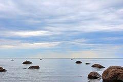Le rivage ou la banque du Golfe finlandais près de Petersbourg pendant le jour d'été nuageux avec les roches et les pierres Photographie stock libre de droits