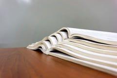 Le riviste aperte si trovano sopra a vicenda su una tavola marrone, documenti sono primo piano impilato fotografia stock