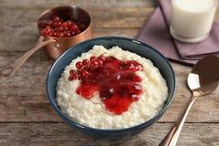 Le riz au lait crémeux avec la groseille rouge et la confiture dans la cuvette a servi images libres de droits